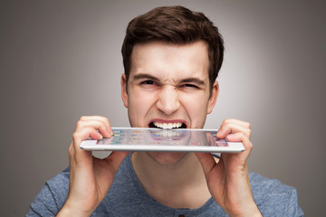 Man biting digital tablet