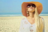 Beautiful blond woman on the beach in the hat and sunglasses