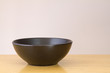 Black bowl on wooden table