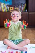 Cute little boy showing his colorful palms