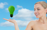 Smiling woman looking at green light bulb
