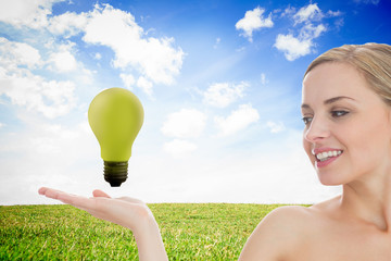 Blonde woman presenting green bulb