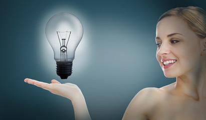 Big light bulb lighting inside hand