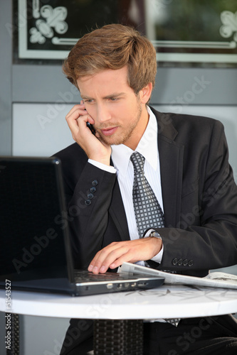 Young contractor with laptop and cell phone