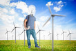 Student with a light bulb head in middle of wind turbine field