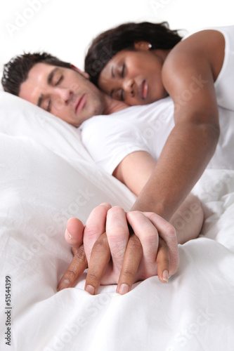 Young couple asleep holding hands in bed