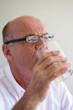 Elderly man drinking a glass of water