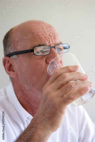 Elderly man drinking a glass of water