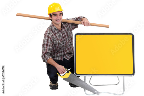 Man kneeling by sign holding saw and plank of wood