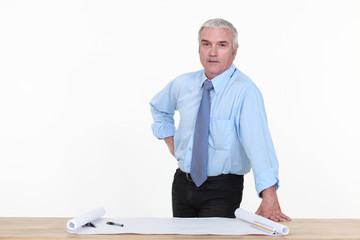 Grey-haired architect stood by work desk