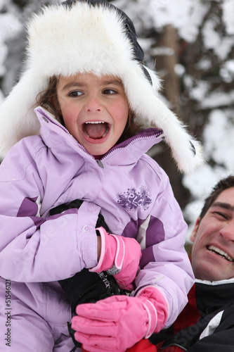 Father and daughter having fun in the snow