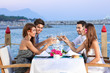 Friends celebrating at a seaside restaurant - 51547168