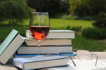 Tisch mit Buecher und Glas Rotwein im Garten.