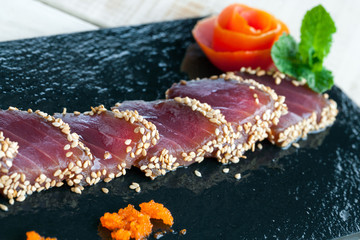 Japanese tataki served on black tile.