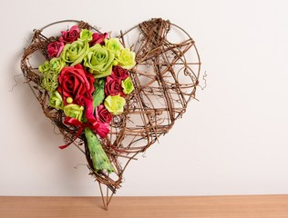 Decorative wicker heart with red and green rose.