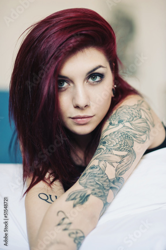 Sensual portrait of beautiful girl with tattoo lying on bed.