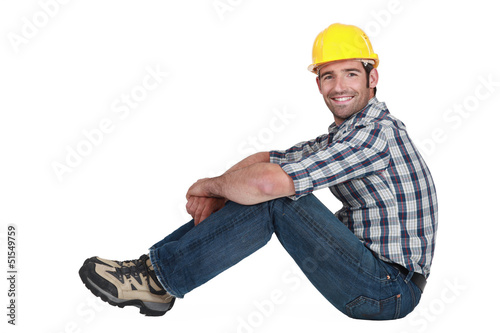A handsome manual worker seated.