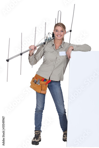 Woman with an aerial leaning against a blank poster