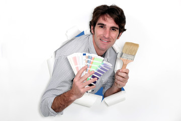 Man holding paint brush and swatch