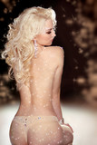Long curly Hair. Back of slim blond woman wearing in twinkled li