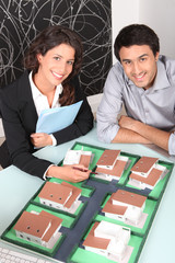 Agent and client looking at a housing model