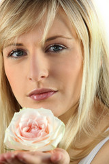 Blonde woman with rose in hand