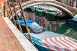 A bridge in Burano island in a canal full of boats