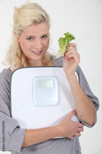 Woman holding lettuce leaf and scales