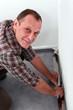 Man adjusting carpet