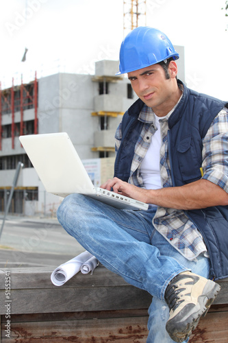 Builder on site with a laptop