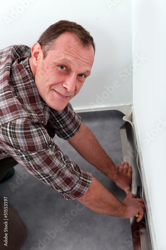 Man adjusting carpet