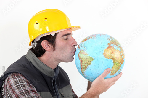 A construction worker kissing a globe.