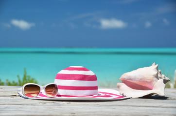 Sunglasses, hat and shell against ocean. Exuma, Bahamas