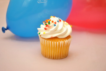Vanilla Cupcake in Front of Balloons