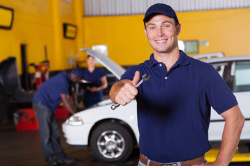 happy male mechanic giving thumb up