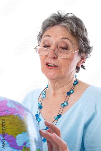 Seniorin geht auf Reisen - ältere Frau isoliert mit Globus