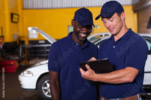happy auto mechanics going through checklist