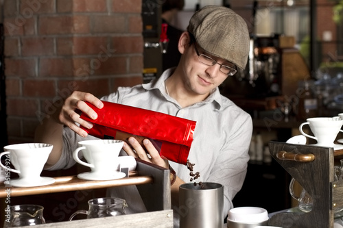 cafe employee pours coffee beans into grinder. focus on beans.