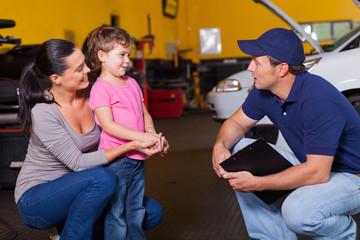 friendly auto technician talking to customer's daughter