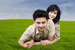 Happy couple lying on green grass