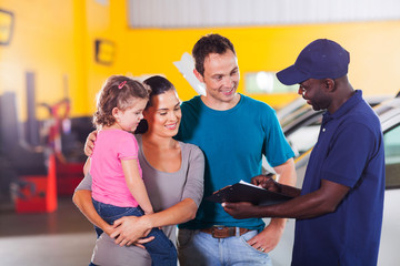 friendly auto mechanic talking to young family