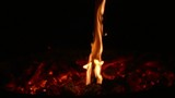 Stick burning on a pile of embers