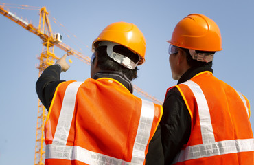 construction workers with crane in background