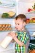 Junge trinkt Milch aus der Flasche vor offenen Kühlschrank