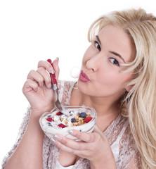 Junge Frau morgens beim Frühstücken: Müsli