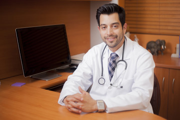 Handsome young physician waiting for a patient in his office