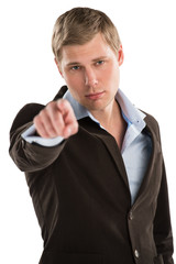 Portrait of an young male business executive pointing at you aga