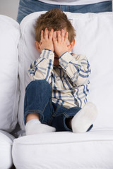 Portrait of little boy closing eyes with his hands at home