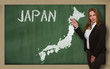 Teacher showing map of japan on blackboard