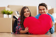 Young couple holding a heart shape pillow